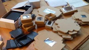 Bruna pappkartonger som inte ännu vikts till fyrkantiga askar. De ligger i högar eller buntar på ett bord.