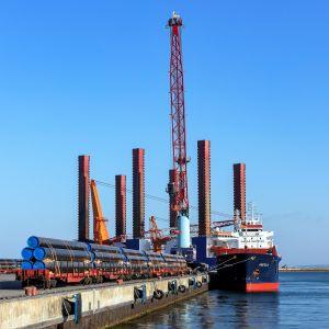 Laiva on satamassa. Laiturilla on putkia odottamassa lastausta.