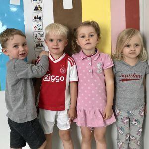Fyra barn i dagisåldern står framför en färgglad planch.
