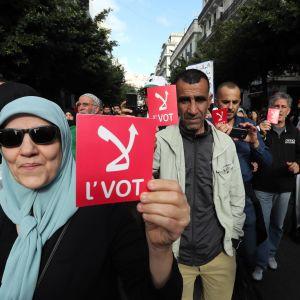 """Demonstranter i Algeriet håller upp lappar med texten """"nej""""."""