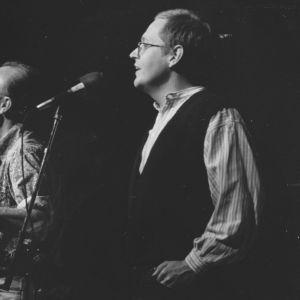 Pete Seeger ja Mikko Perkoila kuvattuna Vanhan ylioppilastalon lavalla kesken lauluesityksen.