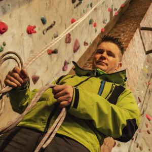 Man i neongrön jacka håller i ett rep. I bakgrunden en klättringsvägg.