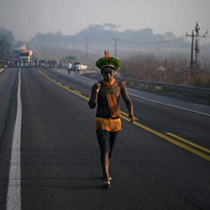 En invånare från ursprungsbefolkningen i Amazonas som promenerar på en landsväg som blockerats.