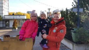En man iklädd orange jacka håller ett litet barn, till vänste om paret poserar en flicka iklädd en ljusröd overall.