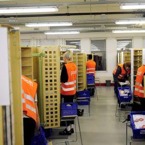 Postens anställda iklädda orange västar står i bås och sorterar post.