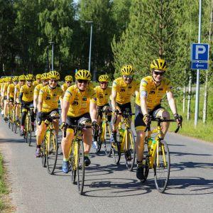 Team Rynkebyn Oulun-joukkue pyöräilee keltasissa pyöräilyvarusteissaan kesämaisemassa.
