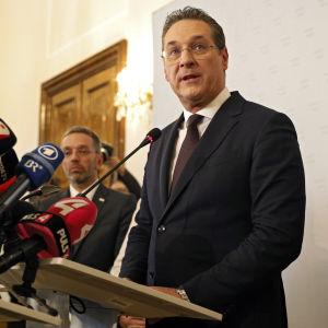 Strache står och talar i en talarstol full med mikrofoner.