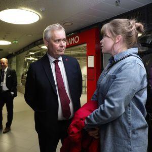 Minister Antti Rinne i mitten lyssnar på en kvinna till höger.