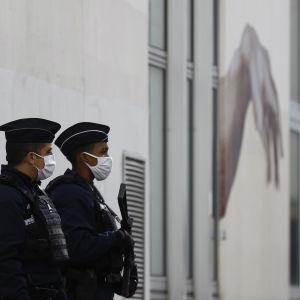 Kaksi poliisia vartioimassa rakennusta.
