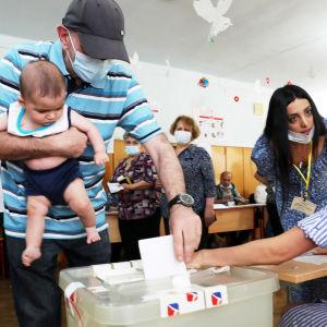 Mies äänestää vauva sylissään.