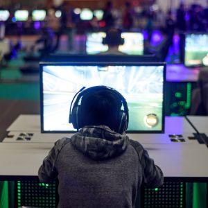 En person med stora hörlurar framför en dataskärm