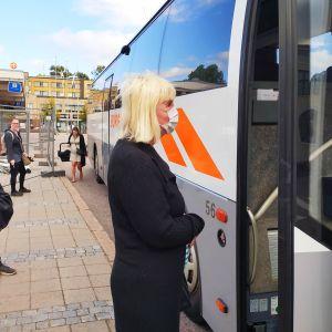 Kvinna bär vitt ansiktsskydd vid en buss med öppen dörr.