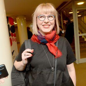 En leende kvinna med en ryggsäck på axeln.