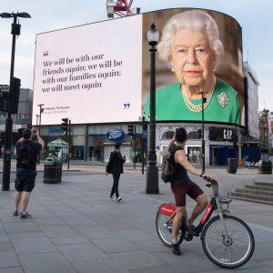 """Fotgängare och en cyklist tittar upp mot den stora skärmen vid Piccadilly Circus som pryds av drottning Elizabeths porträtt och citatet """"We will be with our friends again; we will be with our families again; we will meet again."""