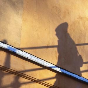En persons skugga på en husvägg.