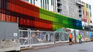 Bild på det nya, ännu halvfärdiga barnsjukhusets fasad. Framför det stängsel och två buggarbetare.