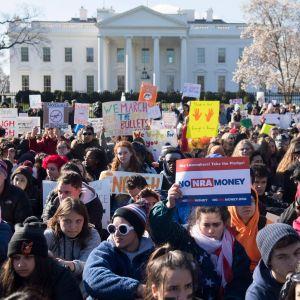 Hundratals elever med protestplakat sitter utanför Vita huset.