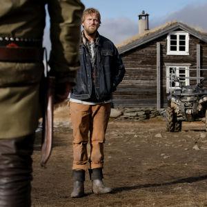 På bilden syns norska skådespelaren Tobias Santelmann som står framför ett trähus i fjällmiljö.
