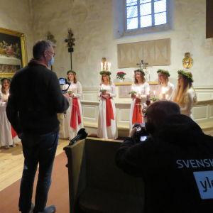 En man bandar lucia och tärnor inne i en kyrka, Yles tekniker filmar i sin tur mannen som filmar. Båda männen har munskydd.