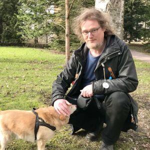 Johanni Larjanko klappar sin hund. Parkmiljö.