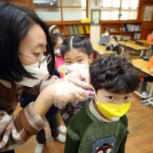 Opettaja mittaa hengityssuojaimeen pukeutuneelta oppilaalta kuumeen Seoulissa Etelä-Koreassa 30. tammikuuta 2020.