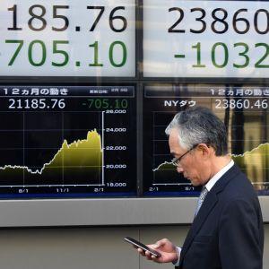 En fotgängare framför börskurstavlor i Tokyo 9.2.2018.