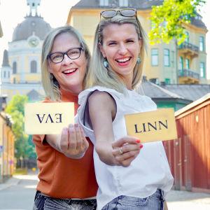 Eva Biaudet och Linn Jung på solig trähusgata i Stockholm med handskrivna namnlappar i händerna. Evas lapp är uppochned.