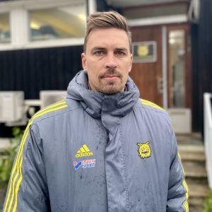Ilveksen päävalmentaja Toni Kallio potretissa jalkapallojoukkueen pukusuojan edessä.