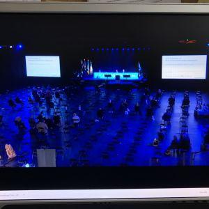 Foto från datorskärm: Samlingspartiet samlas till partikongress i stor, tom sal i Björneborg.