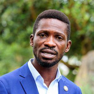 Bobi Wine puhuu. Hänellä on sininen pikkutakki ja vaaleansininen kauluspaita. Takinkaulusliepeessä on pyöreä pinssi.