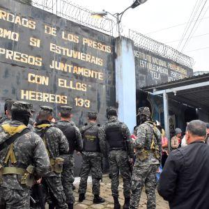 Soldater i utrustning fotade bakifrån. De står utanför en fängelsemur och väntar på att släppas in på området.