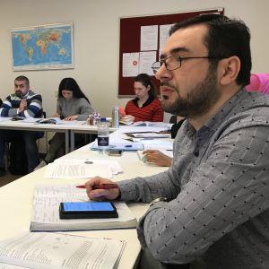 Sazkhan Amizguliyev i ett klassrum med andra invandrare som lär sig danska.