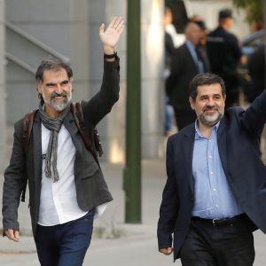 Jordi Cuixart (till vänster) som leder organisationen Omnium och ledaren för ANC, Jordi Sanchez, vinkade utanför Spaniens högsta brottmålsdomstol i Madrid innan de häktades.