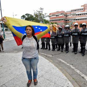 En demonstrant håller Venezuelas flagga framför en rad kravallpoliser