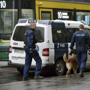Två poliser och en polishund framför en parkerad polisbil på gatan.