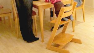 barn i matstol med förälder bredvid