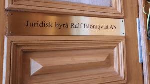 Gyllene skylt där det står juridisk byrå Ralf Blomqvist Ab.