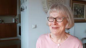 Anita Jansson, en dam med grånande hår, glasögon och en rosa tröja.