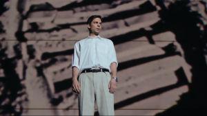 Närbild på Jari Sarasvuo (Mikko Nousiainen) då han står på en stor scen.