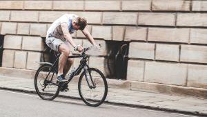 Mies polkee pyörällä, asento viittaa väsymykseen.