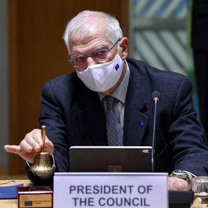 Maskikasvoinen Josep Borrell soitaa kelloa neuvottelupöydän ääressä