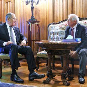 Sergei Lavrov istuu tuolilla ja Josep Borrell sohvalla. Lavrov puhuu juuri, Borrell kuuntelee. Miehillä on tummat puvut, kravatit. Heidän edessään on pieni pöytä, jossa kaksi vesipulloa ja paketti, mahdollisesi kasvomaskeja.
