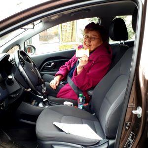 vanha nainen autossa näyttää karkkiaskia
