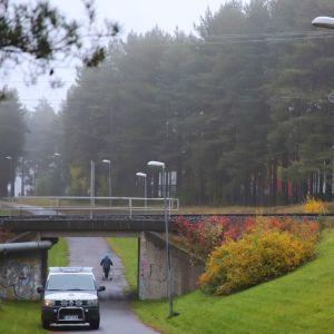 En polisbil står parkerad längs en cykelväg nära en mindre bro.