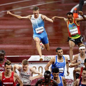 Topi Raitanen tar sig över ett hinder med många löpare framför honom.