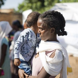 en kvinna håller ett barn i famnen