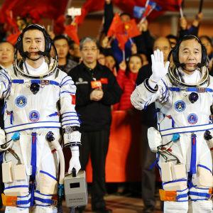 Taikonauterna  Chen Dong (till vänster) och Jin Haipeng vinkar under en ceremoni inför rymdfärden den 17 oktober 2016.