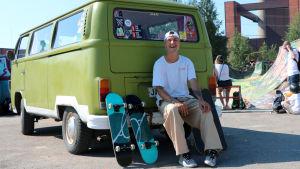 En ung man sitter vid sin gröna bil med rullbrädor brevid sig. Han skrattar. Bilen är parkerad vid en rullbrädspark.
