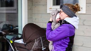 En kvinna i lila jacka håller en baby i famnen. Hon ser ut att pussa babyns hjässa eller tala lugnande till babyn som ser lite missnöjd ut.