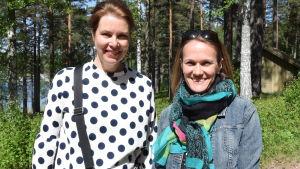 Två kvinnor står bredvid varandra ich tittar leende mot kameran. Utomhus, sommar. Skog och strand och vatten i bakgrunden.